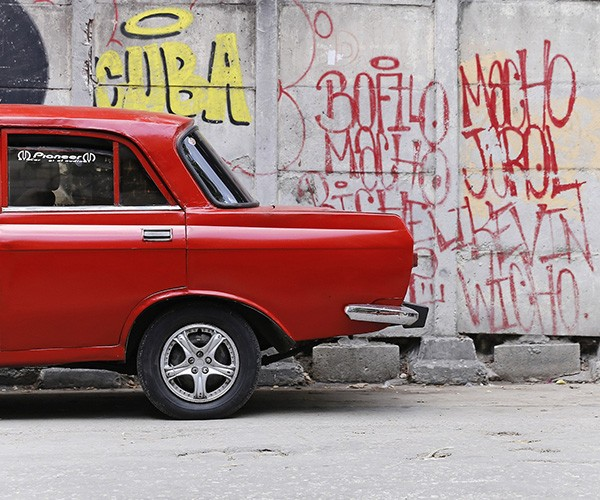 A red car is parked in front of a retaining wall emblazoned with graffiti, including the word Cuba.