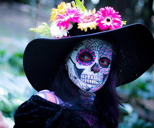 A woman with her face painted to resemble a skeleton wears a large-brimmed black hat covered in bright flowers.