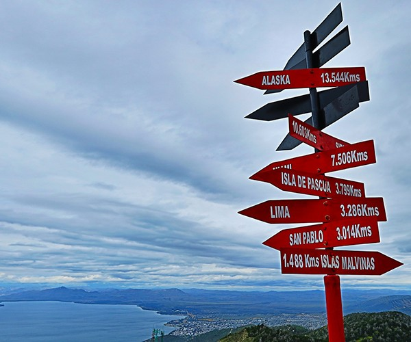 A road sign lists place locations from Alaska to the southernmost point in Argentina and the distances from the sign.