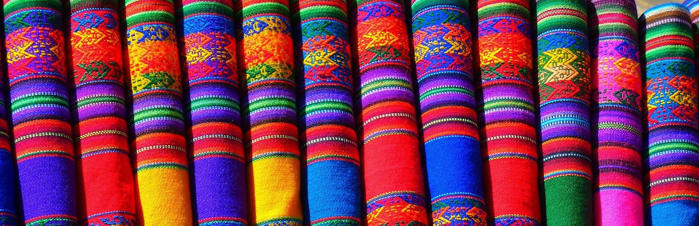 A row of brightly colored, traditional Mexican textiles folded neatly